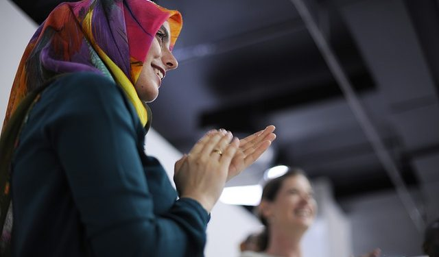 A woman wearing a hijab applauds