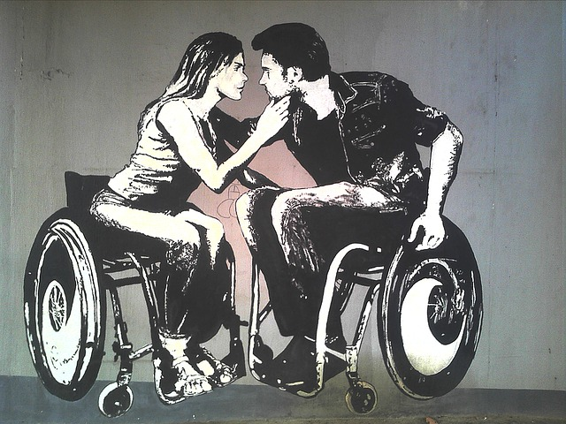 Painted graffiti shows a man and a woman leaning in to kiss each other. They are both wheelchair users